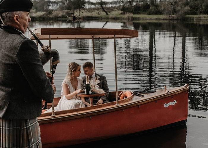 Newlyweds enjoying a ride on a boat with a Scottish piper