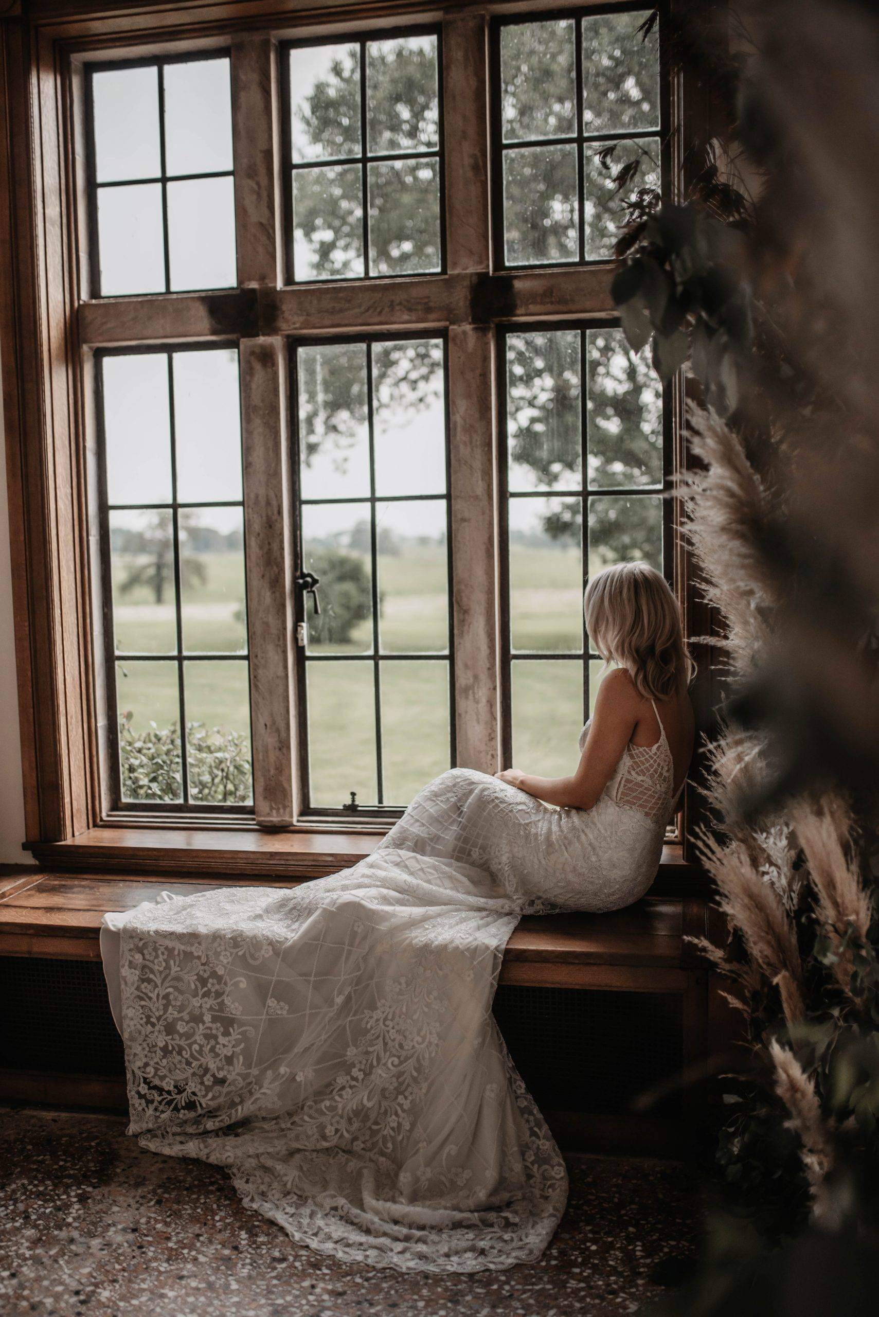 A bride looking out a window on to the private estate