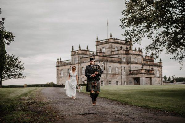 A Scottish piper leading a bride outside Kinmount Castle