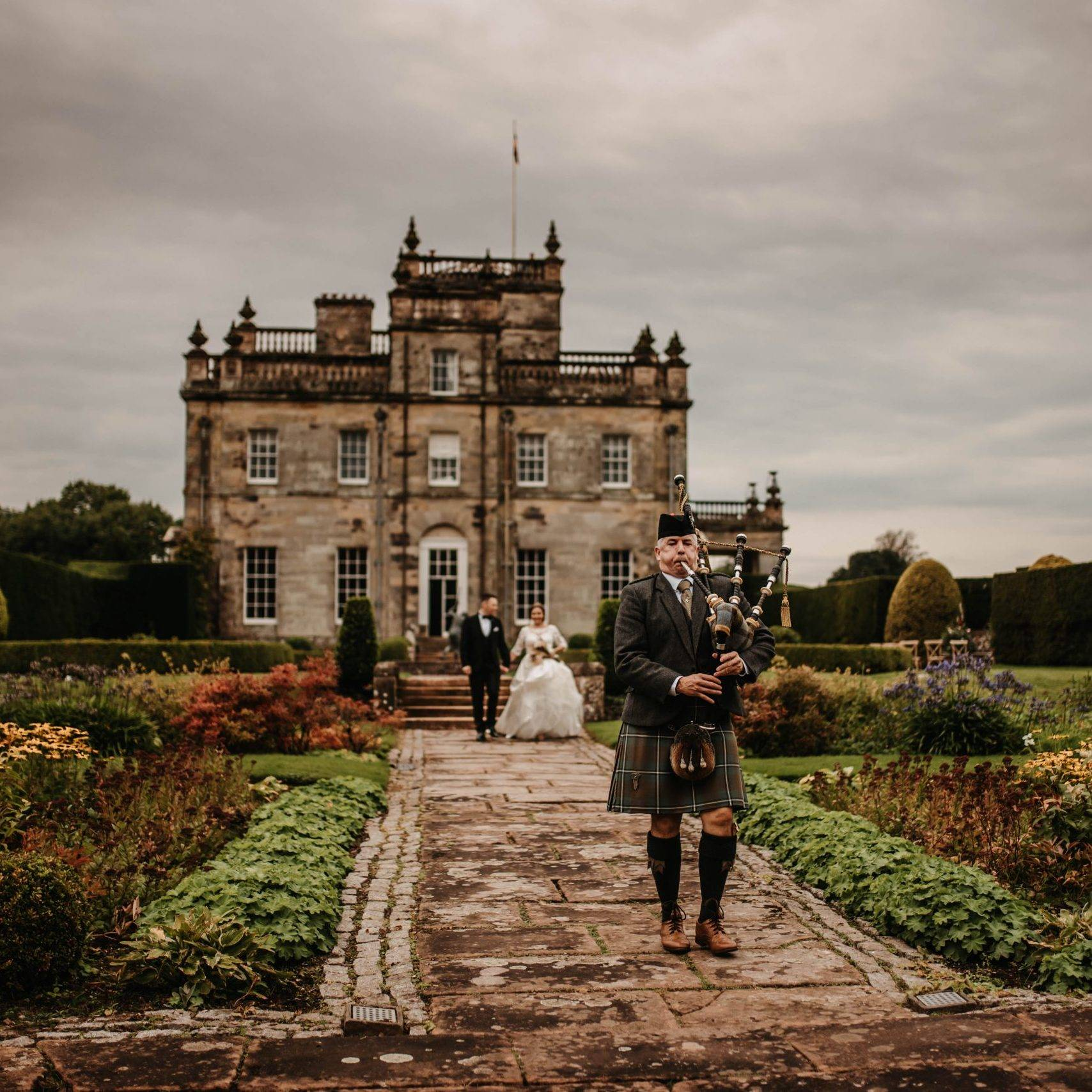 A traditional Scottish piper leading a bride and groom through the Italian Gardens