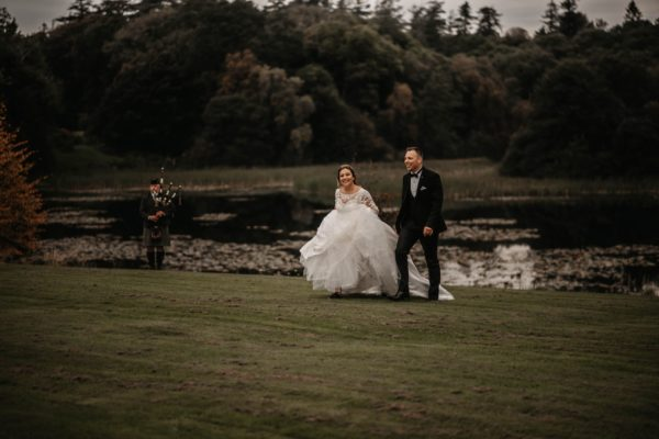 Newlyweds in a field with a Scottish piper