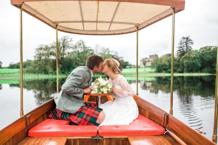 Newlyweds kissing aboard The Good Life motorboat