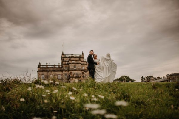 Bride and groom posing in front of Kinmount Castle