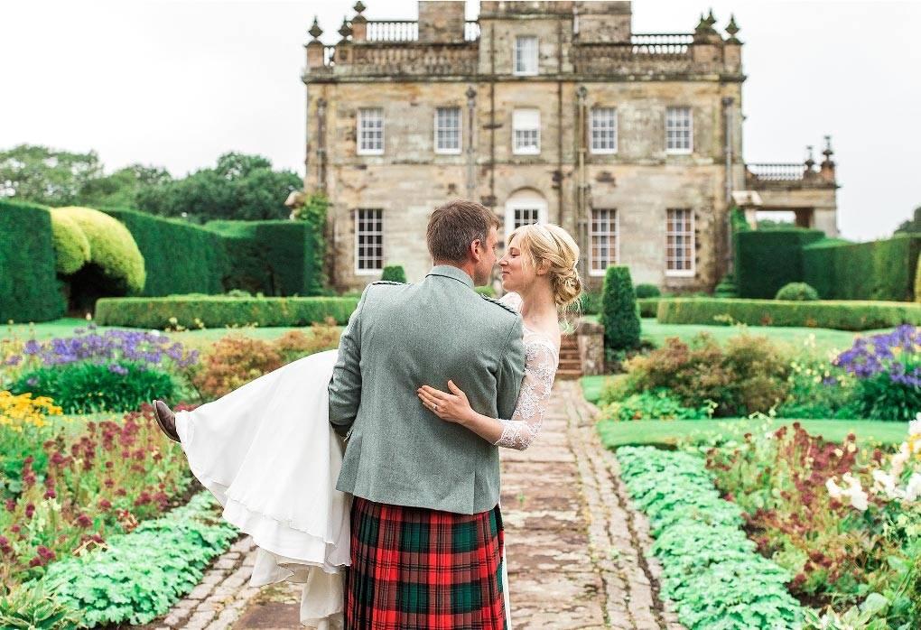 A groom carries his bride through The Italian Garden