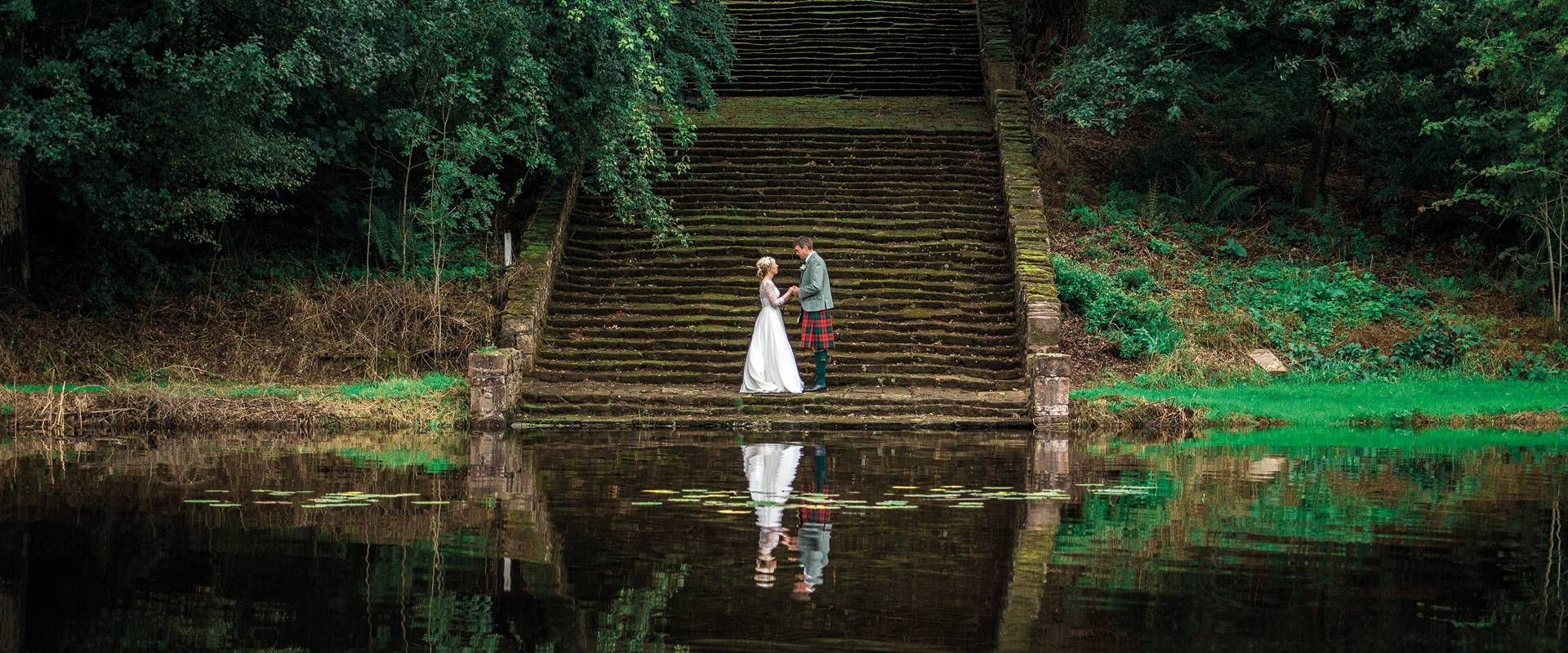 Couple standing at the foot of steps besides a lake