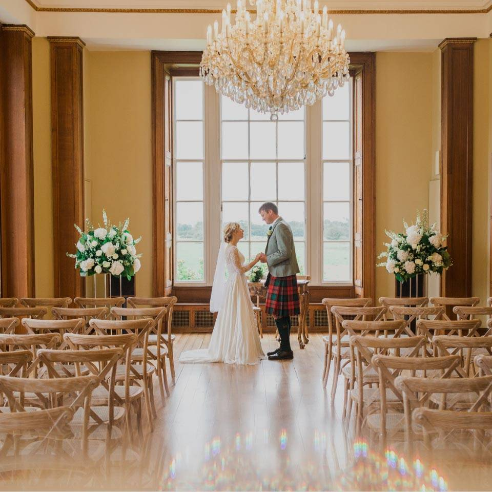 A bride and groom holding hands in The Ballroom
