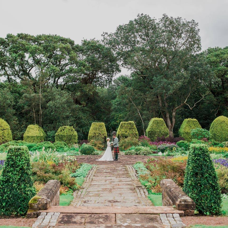 A bride and groom holding hands in the Italian Garden