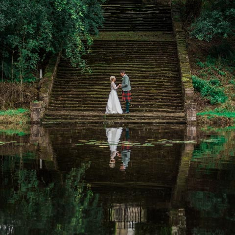 A bride and groom holding hands in at the foot of steps beside a lake