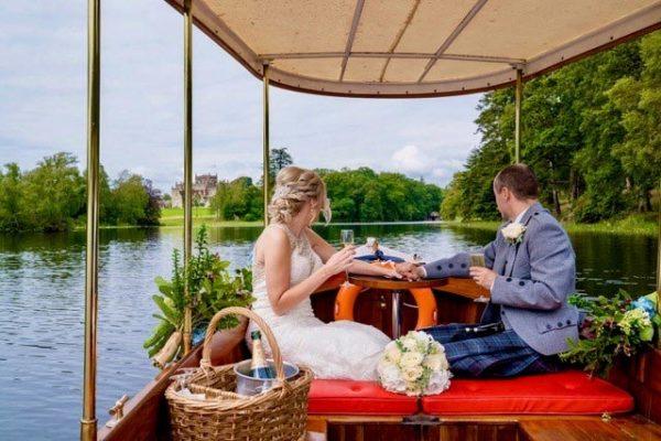 Newlyweds enjoying champagne on a boat ride across a lake